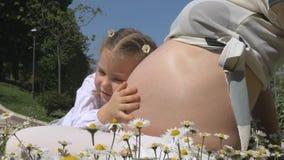 Mujer embarazada con su hija entre las flores en el parque almacen de video