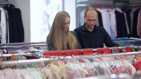 Mujer embarazada con su marido en una tienda de ropa del ` s de los niños La familia feliz elige la ropa para el bebé almacen de video