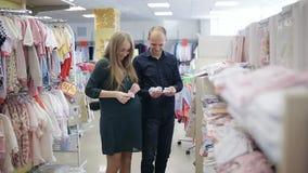 Mujer embarazada con su marido en una tienda de ropa del ` s de los niños La familia feliz elige la ropa para el bebé metrajes