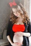 Mujer embarazada con un arco rojo-y-negro grande Imagen de archivo