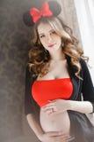 Mujer embarazada con un arco rojo-y-negro grande Imagen de archivo libre de regalías