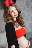 Mujer embarazada con un arco rojo-y-negro grande Foto de archivo