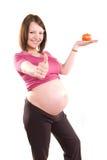 Mujer embarazada con un tomate Imágenes de archivo libres de regalías