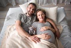 Mujer embarazada de abarcamiento del hombre alegre en cama Fotos de archivo libres de regalías