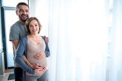 Mujer embarazada de abarcamiento del hombre alegre en casa Fotografía de archivo libre de regalías