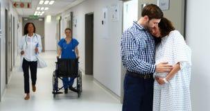 Mujer embarazada de abarcamiento del hombre en pasillo almacen de video