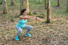 Mujer embarazada de la aptitud que hace las posiciones en cuclillas al aire libre fotografía de archivo