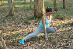 Mujer embarazada de la aptitud que hace la pierna que estira el ejercicio al aire libre imágenes de archivo libres de regalías