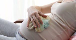 Mujer embarazada de la cosecha con los calcetines minúsculos almacen de video