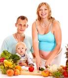 Mujer embarazada de la familia que prepara el alimento. Foto de archivo libre de regalías