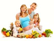 Mujer embarazada de la familia que prepara la comida. Imagen de archivo libre de regalías