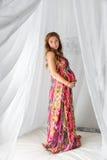 Mujer embarazada de la moda hermosa joven en el vestido colorido que se coloca en una cama con un toldo en un fondo blanco Foto de archivo