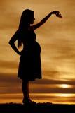 Mujer embarazada de la silueta que sostiene los zapatos de bebé Imágenes de archivo libres de regalías