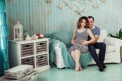 Mujer embarazada de los jóvenes con el marido en el sofá blanco en sitio azul pares vestidos en ropa rayada Inspiración del veran Imagenes de archivo