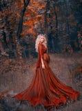 Mujer embarazada de los jóvenes con el pelo rizado rubio en vestido rojo del escarlata del aleteo ligero largo, colocándose en el fotos de archivo