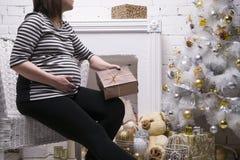 Mujer embarazada de los jóvenes con la caja de regalo que presenta en el fondo del árbol de navidad Foto de archivo libre de regalías
