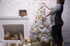 Mujer embarazada de los jóvenes con la caja de regalo que presenta en el fondo del árbol de navidad Fotografía de archivo libre de regalías