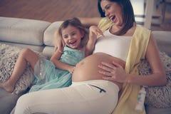 Mujer embarazada de los jóvenes con la hija Fotos de archivo
