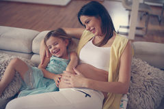 Mujer embarazada de los jóvenes con la hija Foto de archivo