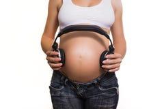 Mujer embarazada de los jóvenes con los auriculares en el vientre Fotos de archivo