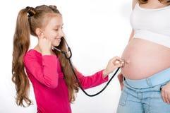 Mujer embarazada de los jóvenes con su hija  Imagenes de archivo
