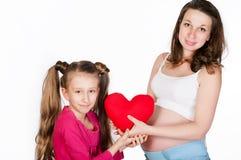 Mujer embarazada de los jóvenes con su hija en el fondo blanco Imagen de archivo