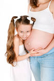 Mujer embarazada de los jóvenes con su hija en el fondo blanco Fotografía de archivo libre de regalías