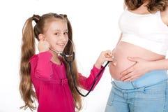 Mujer embarazada de los jóvenes con su hija en el fondo blanco Imagenes de archivo