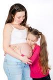 Mujer embarazada de los jóvenes con su hija en el fondo blanco Fotografía de archivo