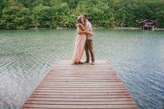 Mujer embarazada de los jóvenes con su marido que coloca el lago cercano Foto de archivo libre de regalías