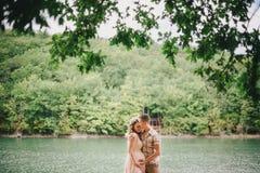 Mujer embarazada de los jóvenes con su marido que coloca el lago cercano Fotografía de archivo