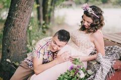 Mujer embarazada de los jóvenes con su marido que se sienta cerca del lago Fotos de archivo libres de regalías