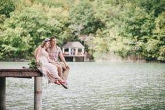 Mujer embarazada de los jóvenes con su marido que se sienta cerca del lago Imagen de archivo