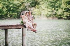 Mujer embarazada de los jóvenes con su marido que se sienta cerca del lago Imagenes de archivo