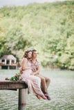 Mujer embarazada de los jóvenes con su marido que se sienta cerca del lago Imagen de archivo libre de regalías