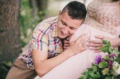 Mujer embarazada de los jóvenes con su marido que se sienta cerca del lago Fotos de archivo