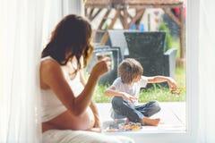Mujer embarazada de los jóvenes, el sentarse interior, mirando a su niño a través Fotos de archivo