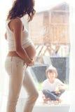 Mujer embarazada de los jóvenes, el sentarse interior, mirando a su niño a través Fotografía de archivo