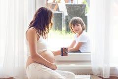 Mujer embarazada de los jóvenes, el sentarse interior, mirando a su niño a través Imagenes de archivo
