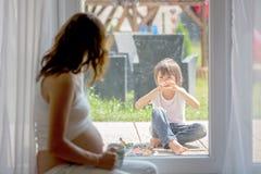 Mujer embarazada de los jóvenes, el sentarse interior, mirando a su niño a través Foto de archivo