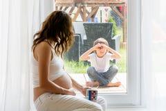 Mujer embarazada de los jóvenes, el sentarse interior, mirando a su niño a través Foto de archivo libre de regalías