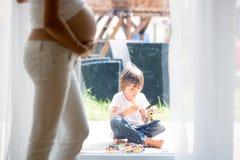 Mujer embarazada de los jóvenes, el sentarse interior, mirando a su niño a través Imágenes de archivo libres de regalías