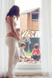Mujer embarazada de los jóvenes, el sentarse interior, mirando su thro de los niños Imagen de archivo libre de regalías