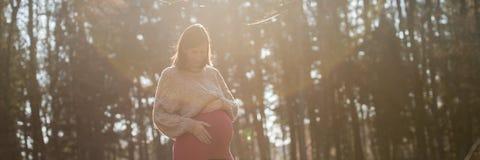 Mujer embarazada de los jóvenes en el trimestre pasado que toca cariñosamente su belio foto de archivo