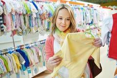 Mujer embarazada de los jóvenes en la tienda de ropa Foto de archivo libre de regalías