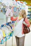 Mujer embarazada de los jóvenes en la tienda de ropa Imagen de archivo