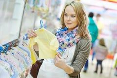 Mujer embarazada de los jóvenes en la tienda de ropa Imágenes de archivo libres de regalías