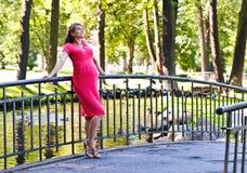 Mujer embarazada de los jóvenes en parque Imagen de archivo libre de regalías