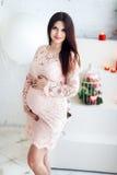 Mujer embarazada de los jóvenes en un vestido rosado contra una pared blanca que mira la cámara Imagen de archivo libre de regalías