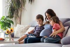 Mujer embarazada de los jóvenes, leyendo un libro en casa a sus dos muchachos Imágenes de archivo libres de regalías